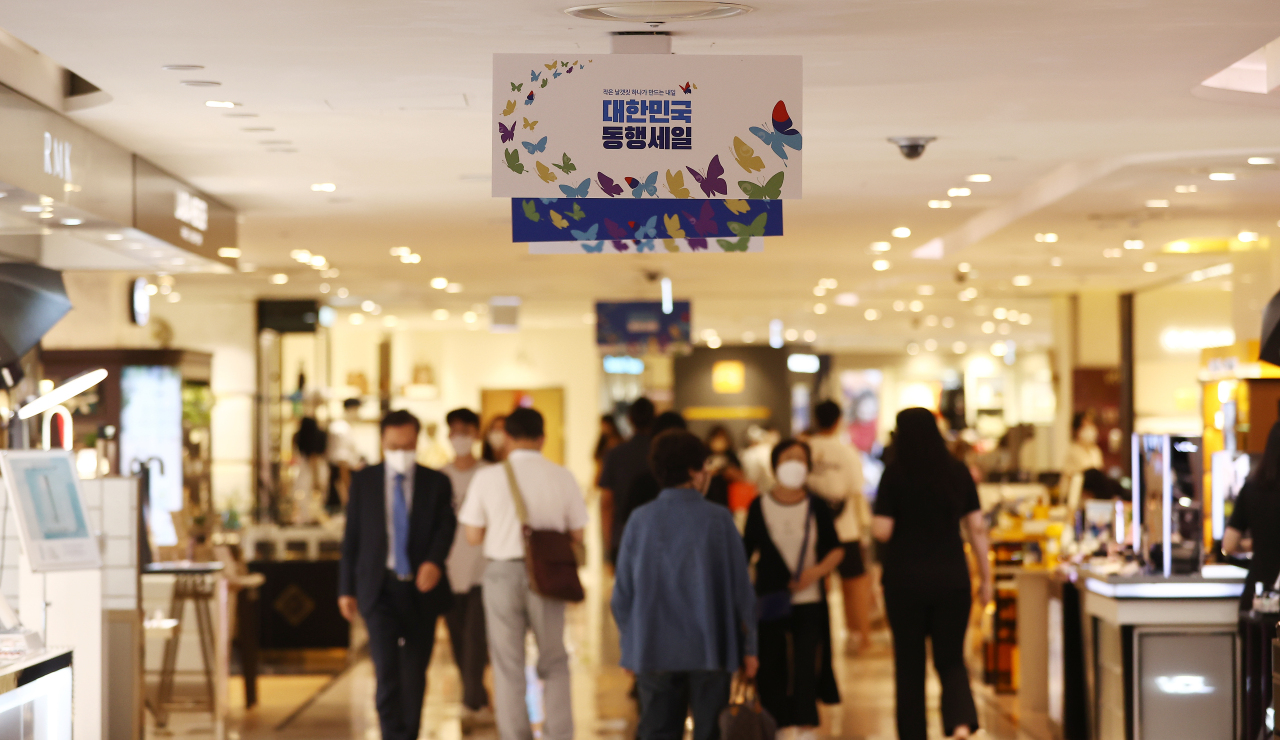 People shop at Lotte Department Store's main outlet in Seoul yesterday, as the country's grand sale event began to support the economy amid the COVID-19 pandemic. (Yonhap)