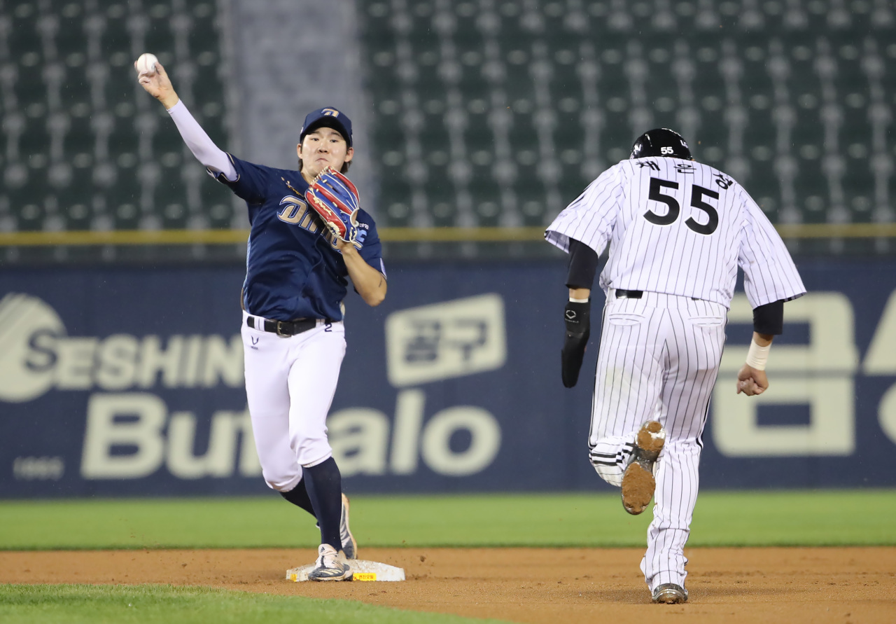 In this file photo from June 10, 2021, NC Dinos' second baseman Park Min-woo (L) throws to first to complete a double play against the LG Twins in the bottom of the fifth inning of a Korea Baseball Organization regular season game at Jamsil Baseball Stadium in Seoul. (Yonhap)