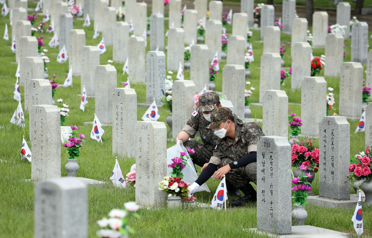 Service members clean the tombstones of South Korean soldiers who were killed during the Korean War at the national cemetery in Seoul on Friday, as the country marked the 71st anniversary of the 1950-53 war. (Yonhap)