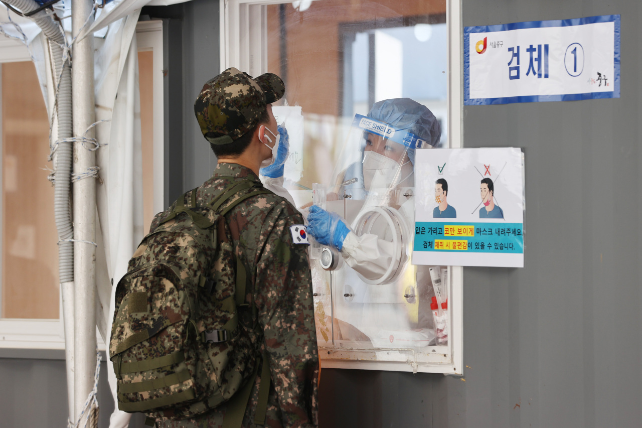 A service member receives a coronavirus test at a makeshift virus test center at Seoul Station on June 20, 2021. (Yonhap)