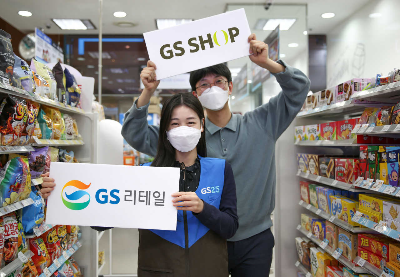 GS Retail employees pose with placards of the logos of GS Retail and GS Home Shopping. (GS Retail)