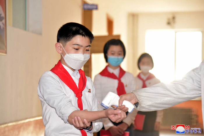 Schoolchildren in Pyongyang undergo temperature checks before entering their classroom, in this photo released by North Korea's official Korean Central News Agency on May 16, 2021. (Korean Central News Agency)