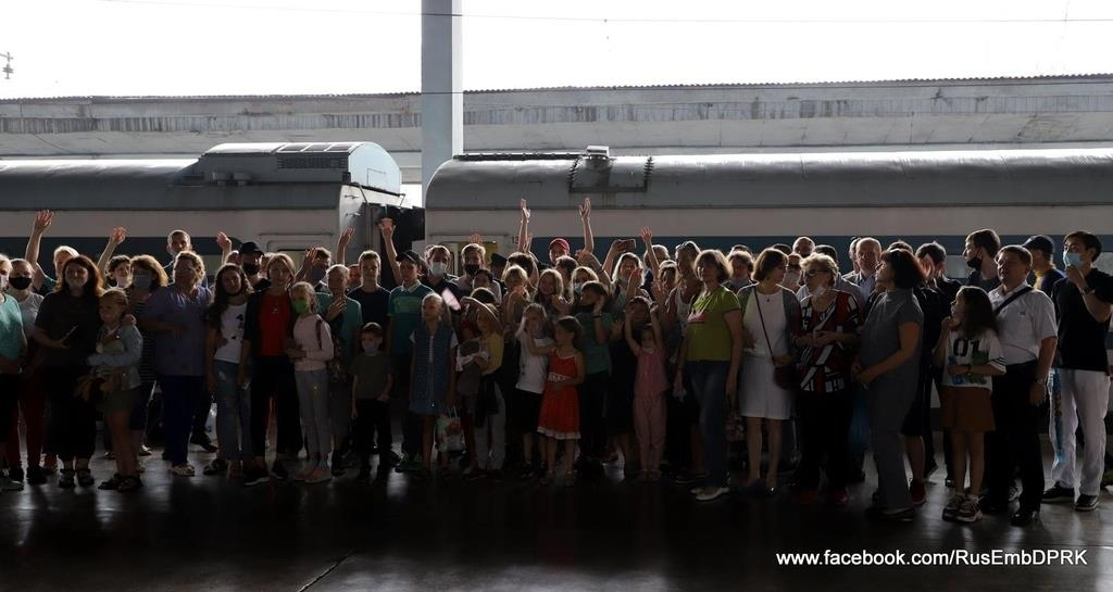 Dozens of Russians wave their hands in front of a train as they prepare to return home at Pyongyang Station in this undated photo captured from the Facebook account of the Russian Embassy in Pyongyang on Tuesday. (Facebook account of the Russian Embassy in Pyongyang)