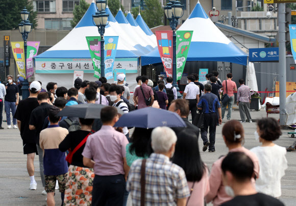 Citizens wait in a long line to receive COVID-19 tests at a temporary testing center at Seoul Station. (Yonhap)