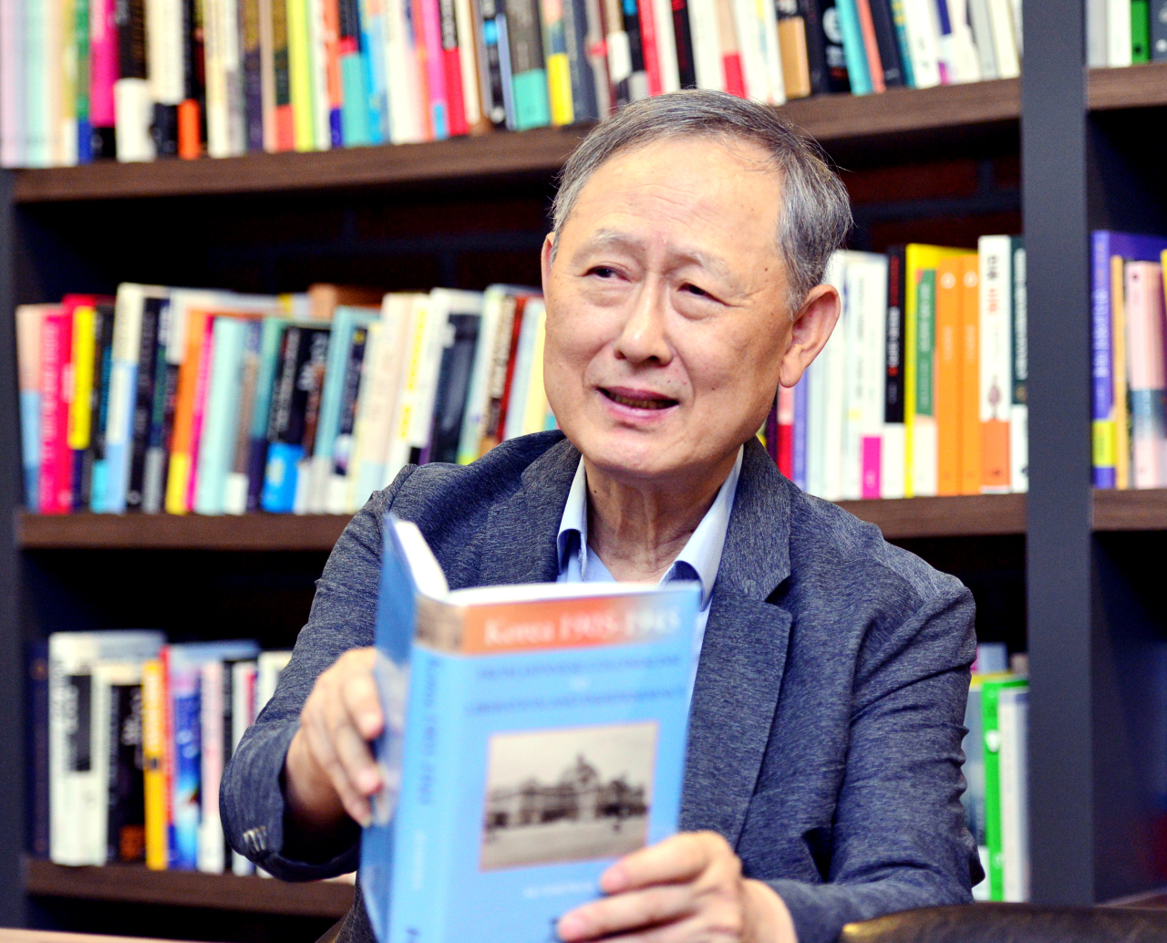 """Professor Ku Dae-yeol poses with his new book """"Korea 1905-1945: From Japanese Colonialism to Liberation and Independence,"""" during an interview with The Korea Herald. (Park Hyun-koo/The Korea Herald)"""