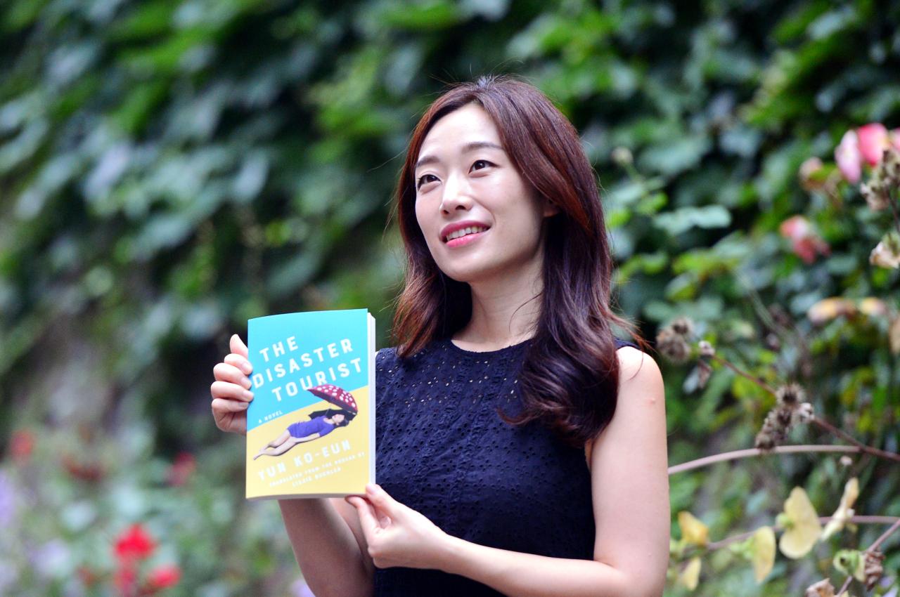 "Yun Ko-eun poses with her book, ""The Disaster Tourist,"" during an interview with The Korea Herald on Wednesday. (Park Hyun-koo/The Korea Herald)"