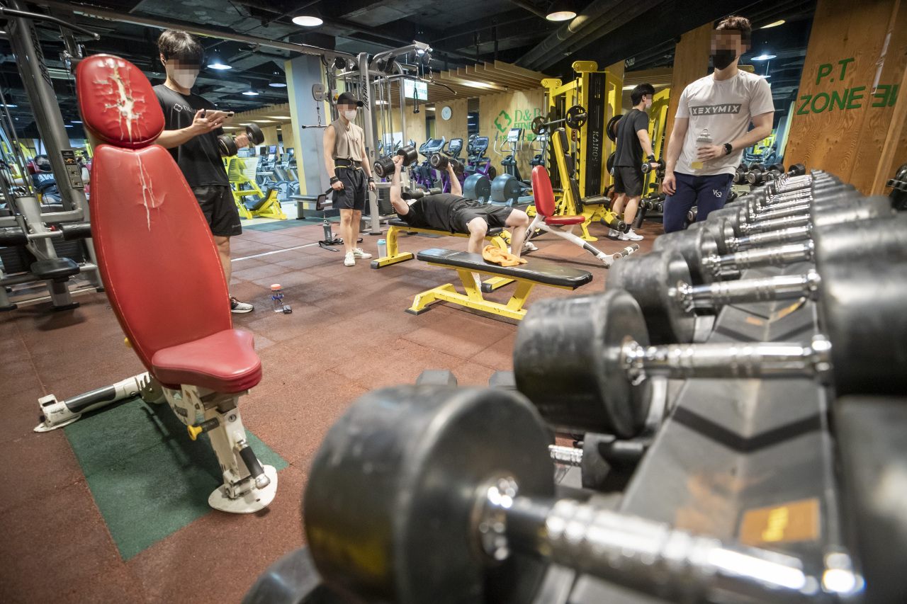 People exercise inside a fitness club in Mapo-gu, western Seoul, last month. (Yonhap)