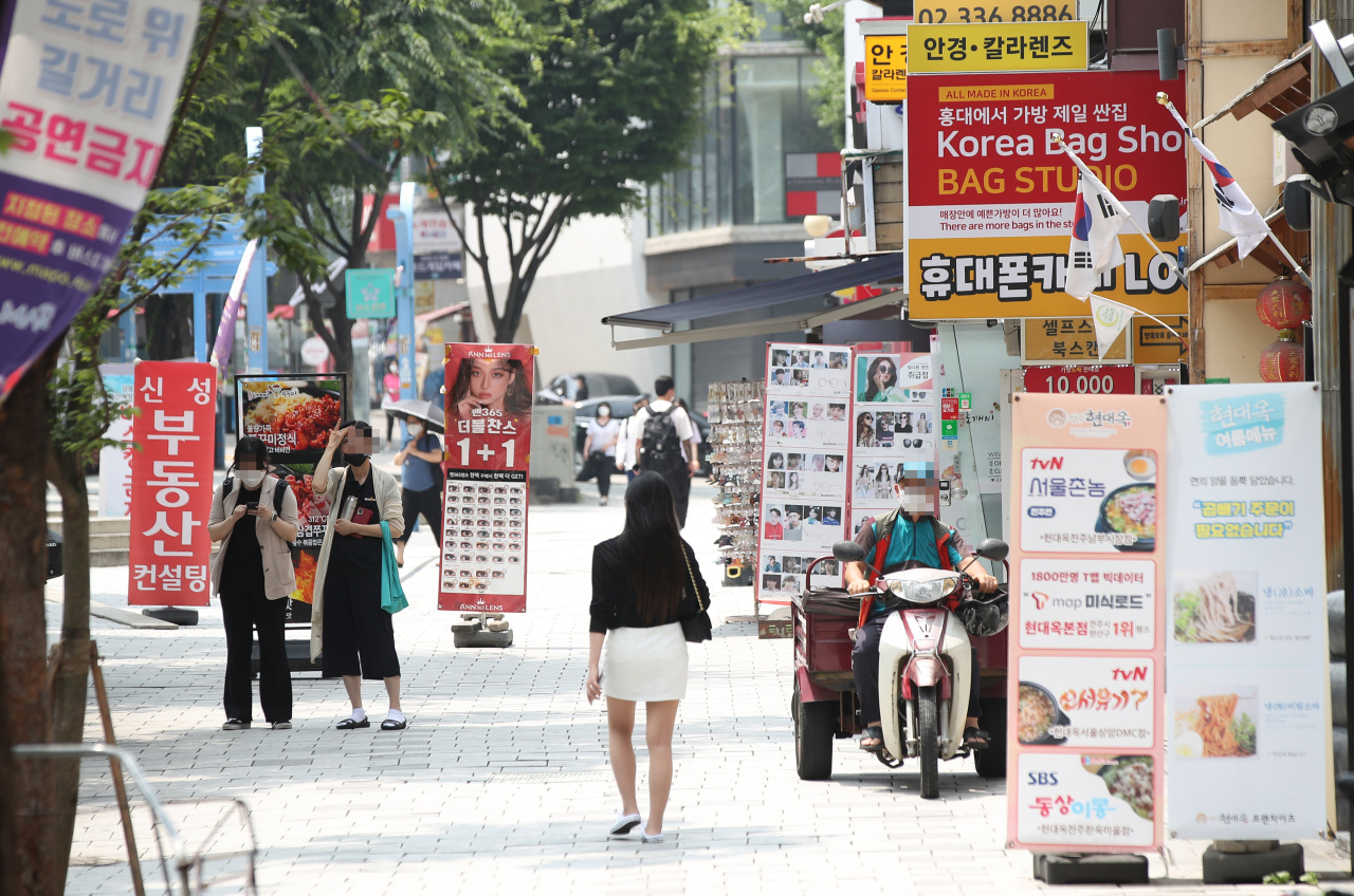 People walk on the street in Hongdae, Seoul, July 1, as the delta variant prompted the government to postpone the planned relaxation of social distancing rules. (Yonhap)