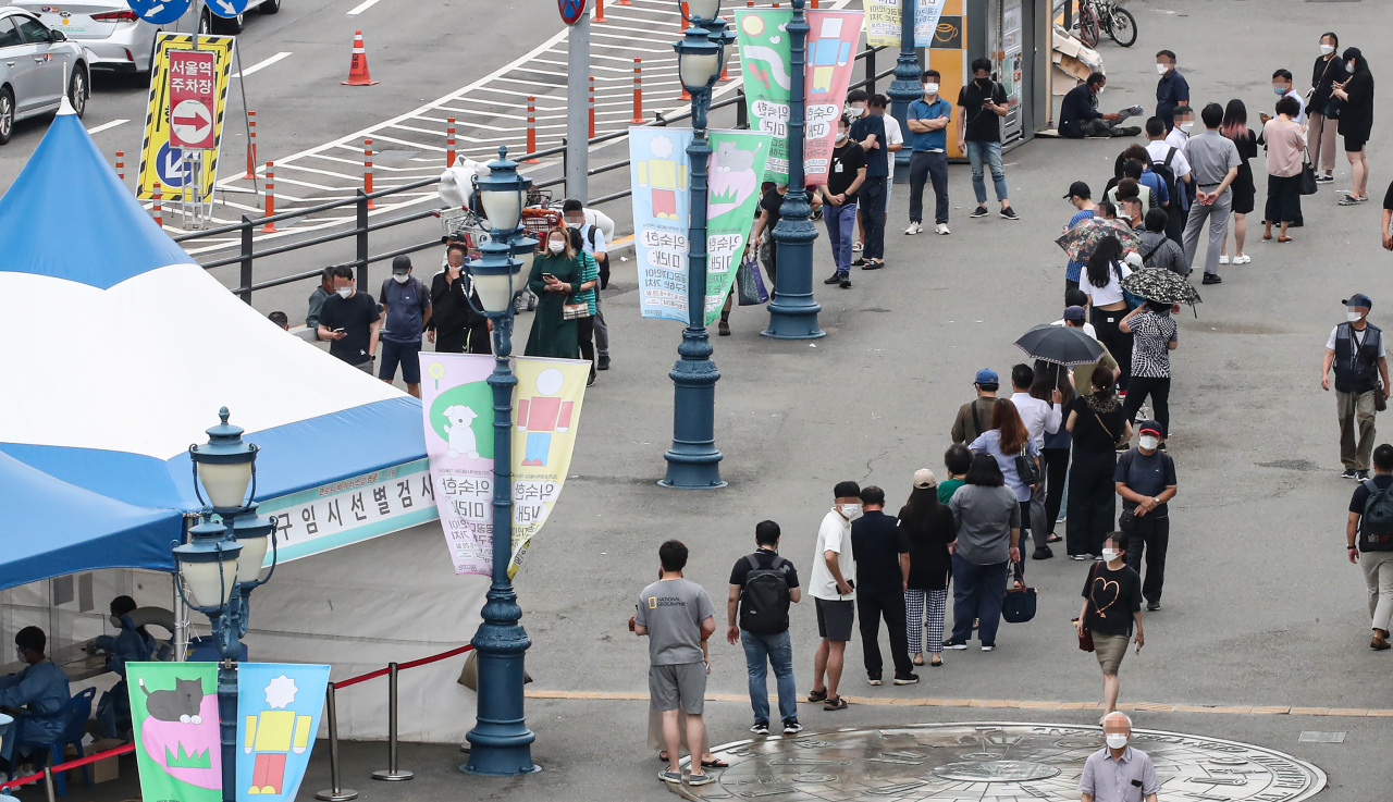 People stand in line to take coronavirus tests at a screening clinic in front of Seoul Station on Tuesday. (Yonhap)