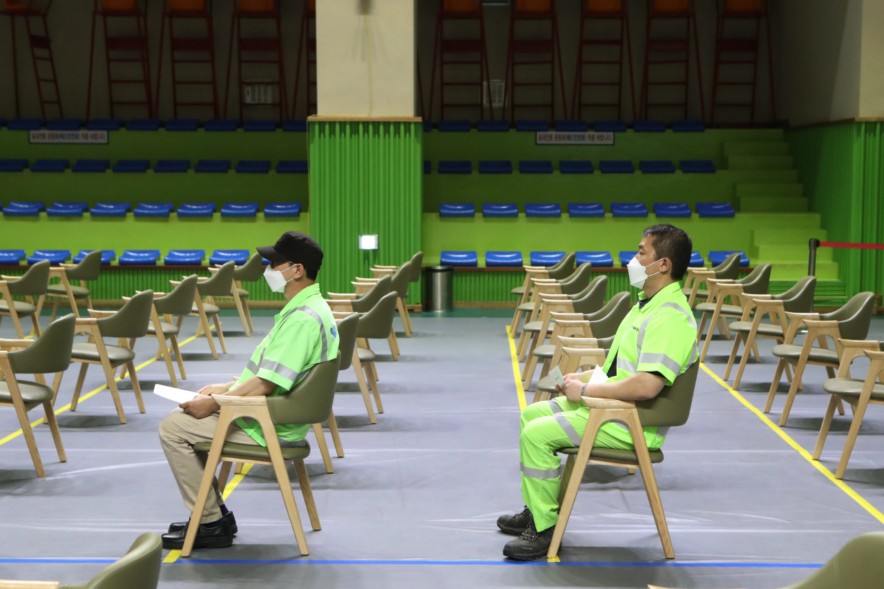 This photo shows members of the essential workforce waiting at a vaccination clinic in Seoul on Tuesday. (Yonhap)