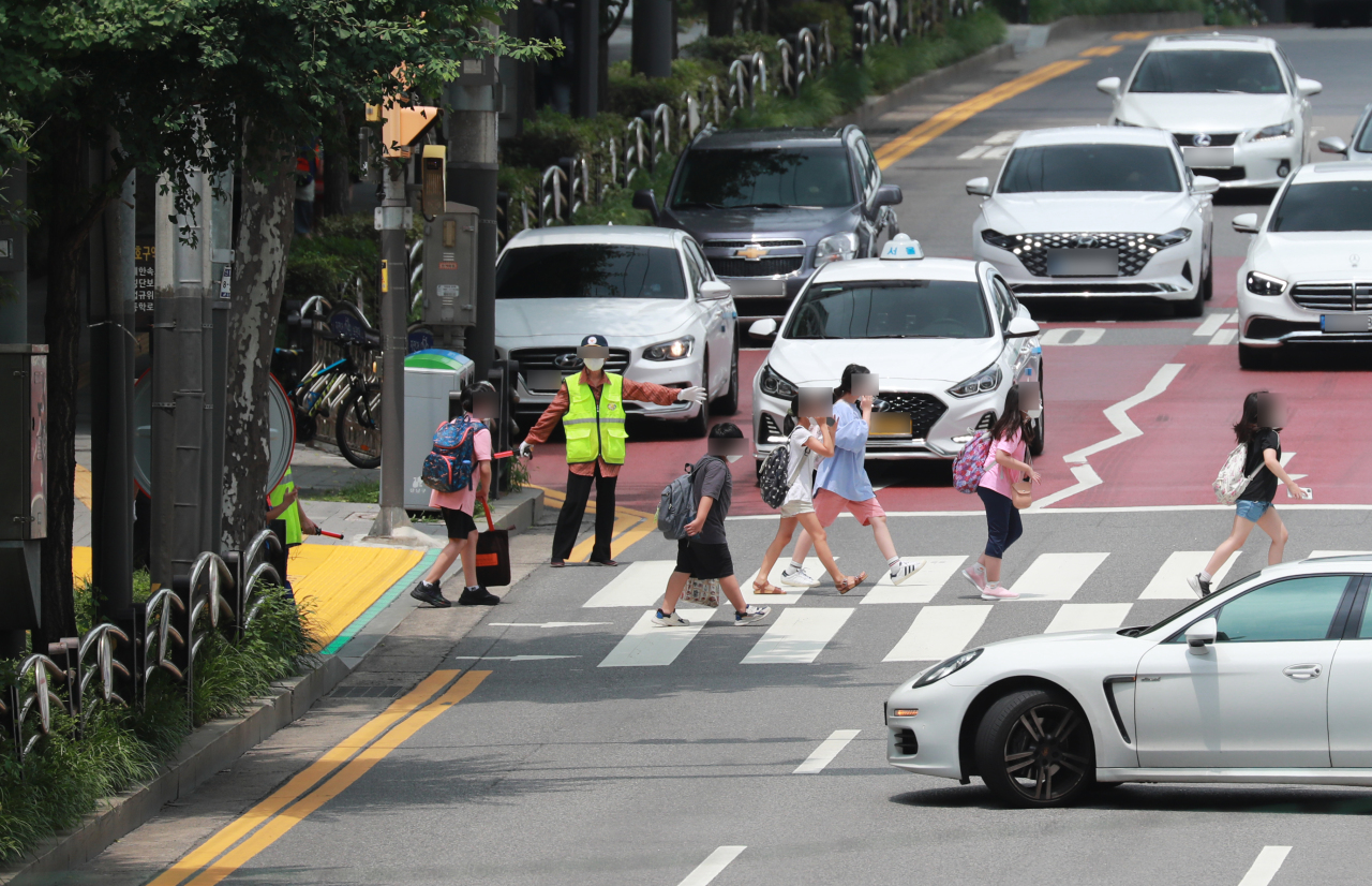 Children go home after school finishes in Seoul last Friday. (Yonhap)