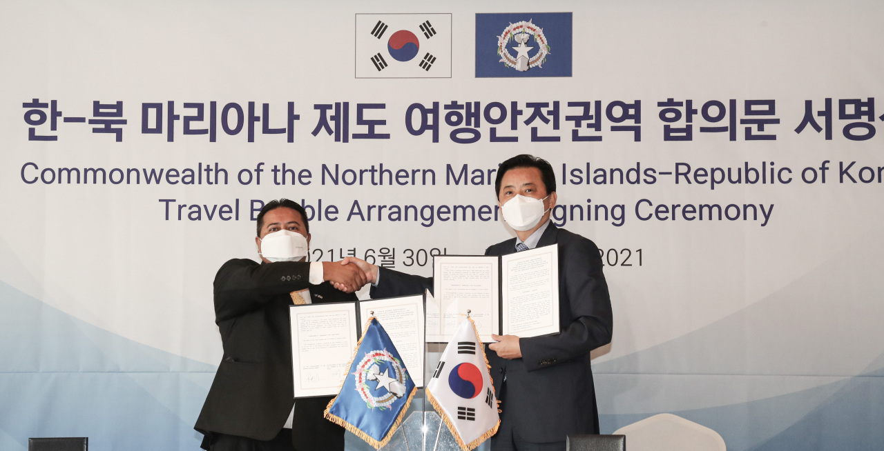 South Korea's Vice Transport Minister Hwang Seong-kyu (R) shakes hands with Saipan's governor Ralph Torres after signing a
