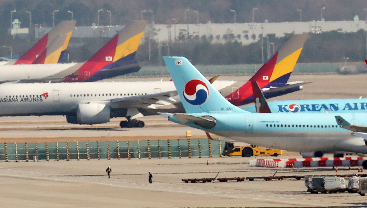 Korean Air and Asiana Airlines planes lined up at a local airport. (Yonhap)