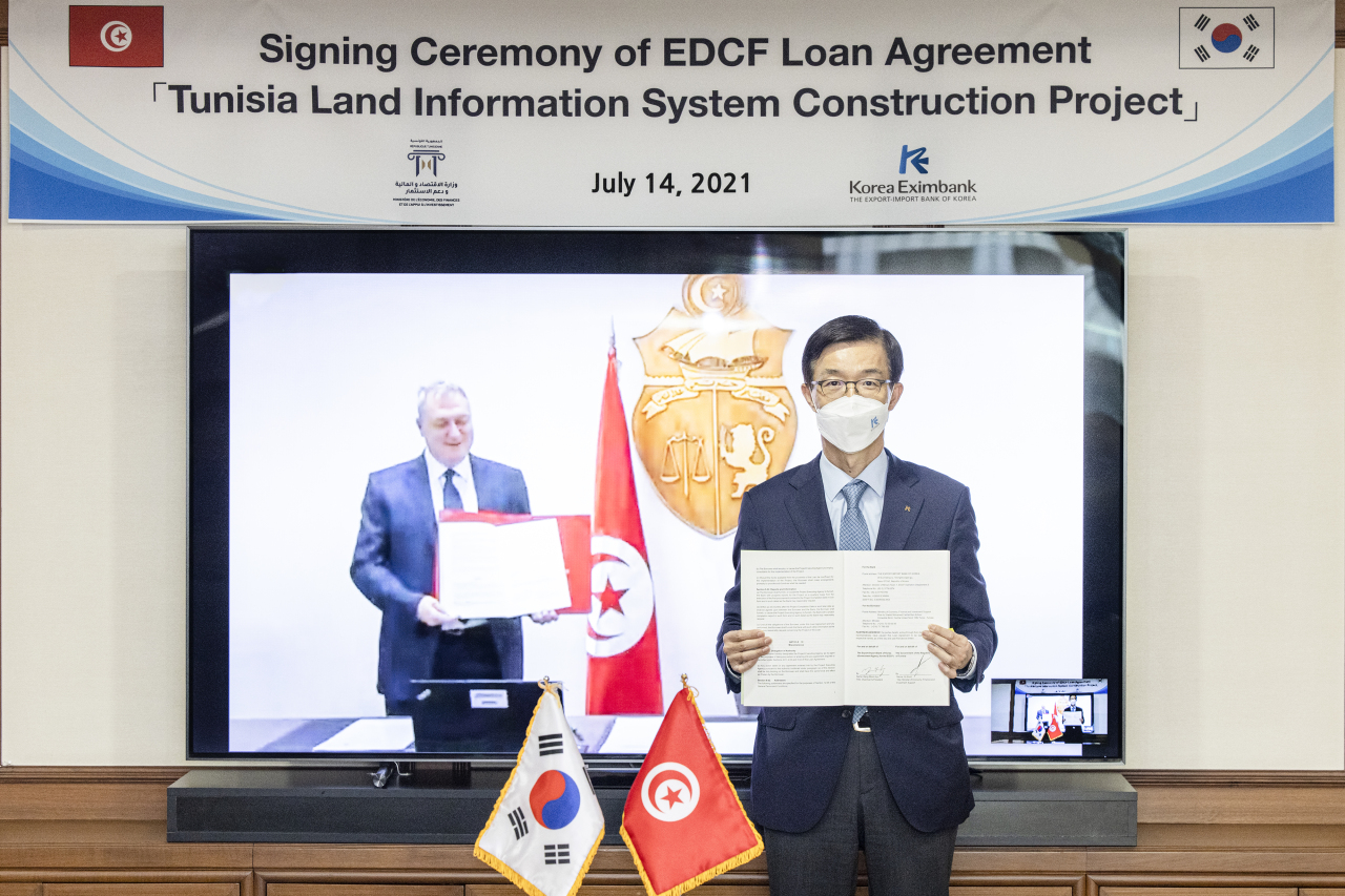 Bang Moon-kyu (right), head of the Export-Import Bank of Korea, and Tunisian Finance Minister Ali Kooli (on screen) pose during an online signing ceremony at the bank's headquarters in Seoul on Wednesday. (Eximbank)