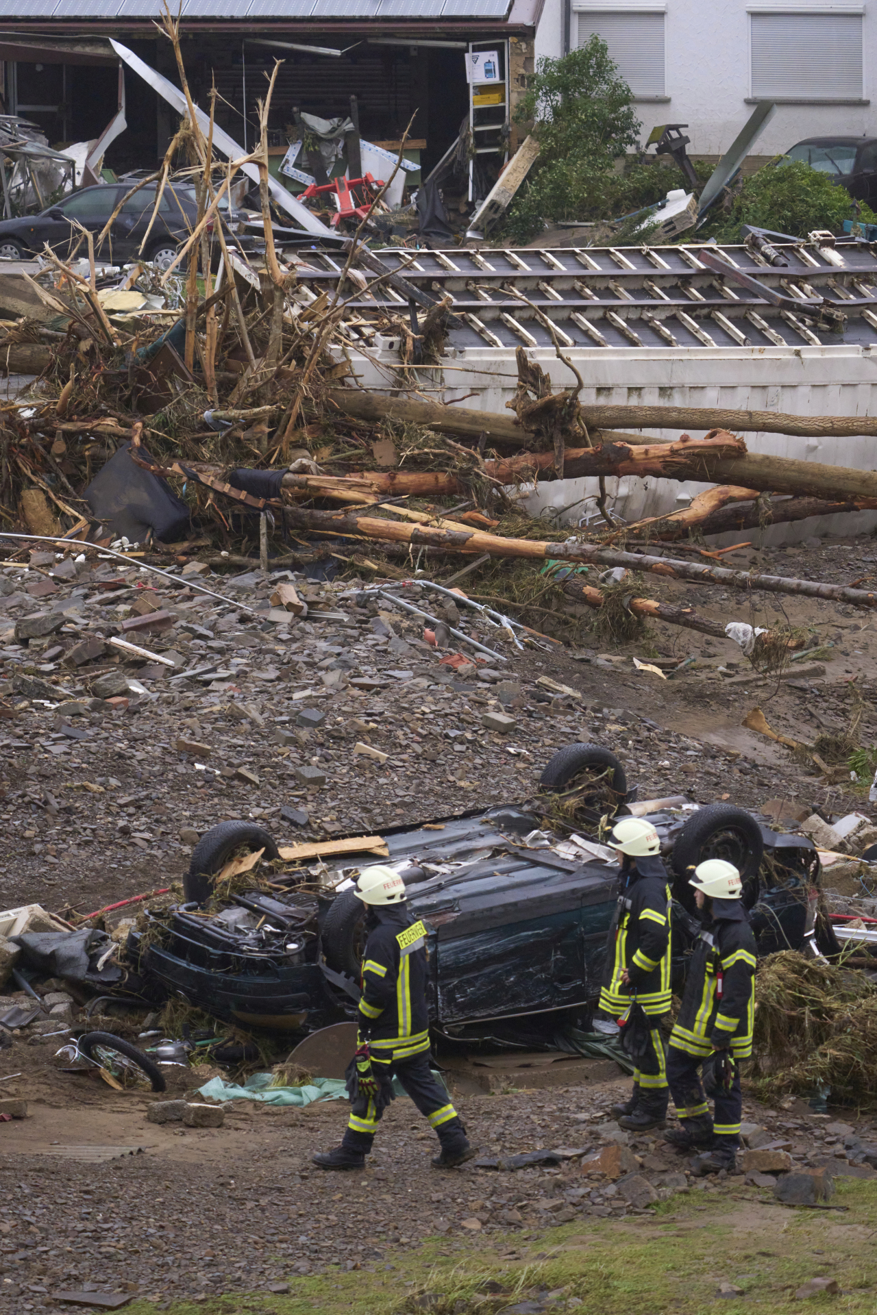 Firefighters walk past a destroyed car in the community of Schuld, Germany, Friday, July 16, 2021. Heavy rains caused mudslides and flooding in the western part of Germany. Multiple have died and dozens are missing as severe flooding in Germany and Belgium turned streams and streets into raging, debris-filled torrents that swept away cars and toppled houses. (AP)