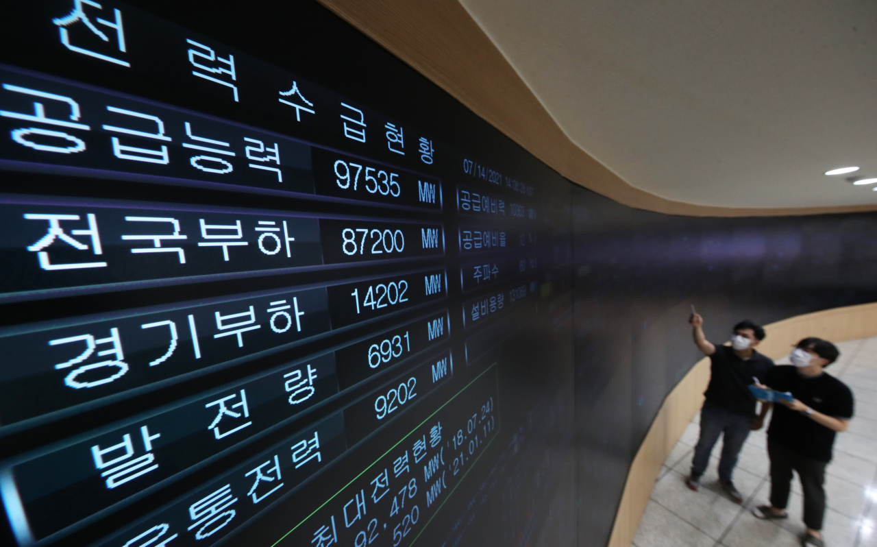 Staffers at Kepco's branch in Suwon, Gyeonggi Province, looks at the screen to check the changes in the demand and supply of electricity. (Yonhap)