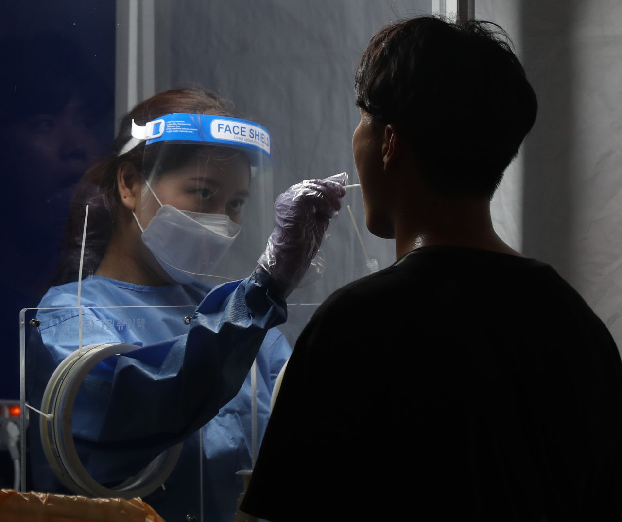 A man goes through a COVID-19 test at a testing site in central Seoul, Thursday. (Yonhap)