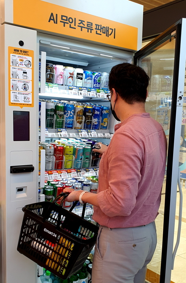 A customer takes out an alcoholic beverage from Emart24's AI-based alcohol vending machine. (Emart24)
