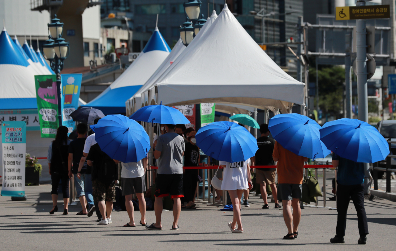 People use umbrellas to protect themselves from the sun while waiting in line at a coronavirus screening center at Seoul Station in downtown Seoul on Sunday. (Yonhap)