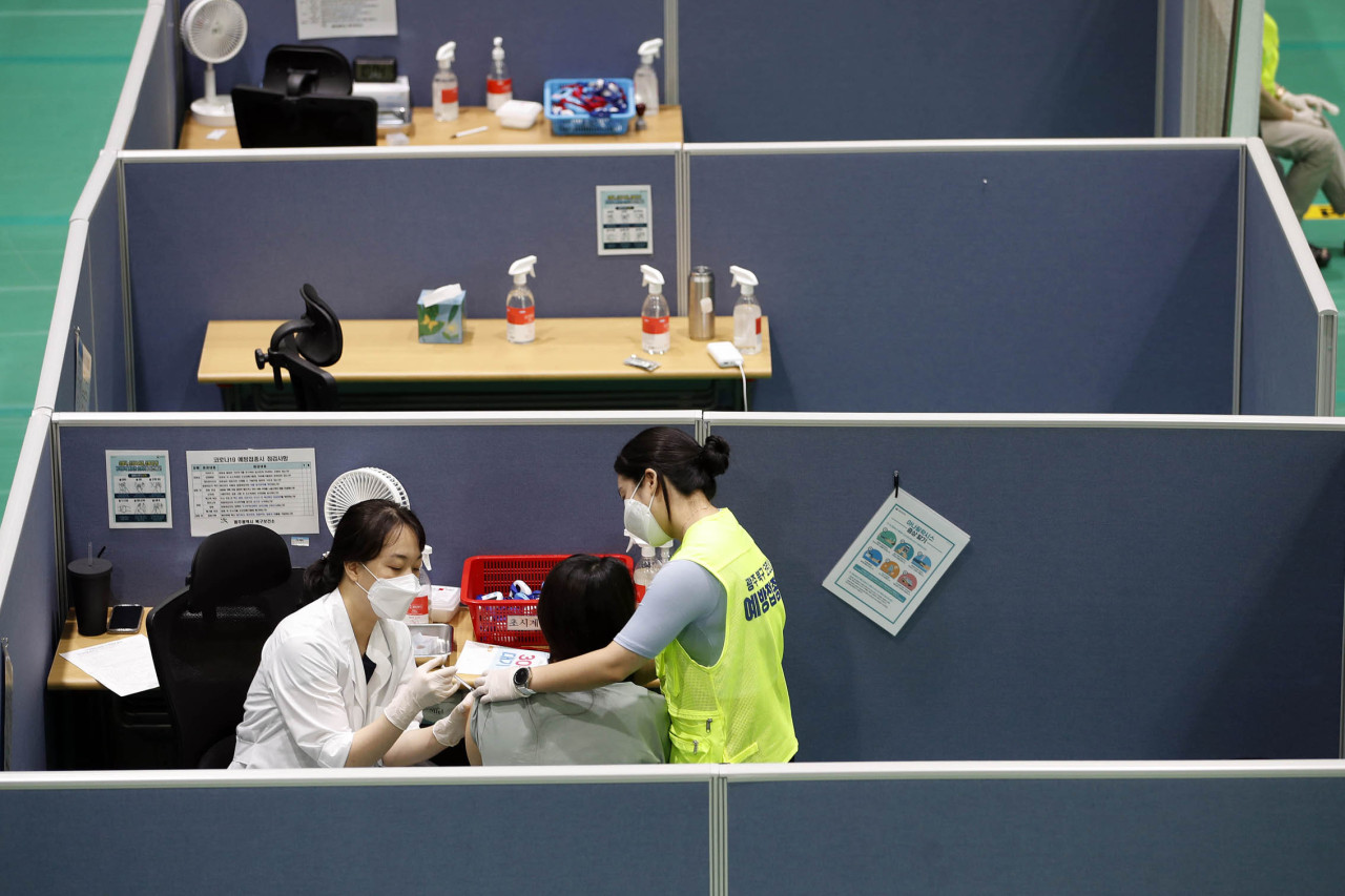 Health care workers at a clinic in Gwangju vaccinate members of the essential workforce on Friday. (Yonhap)