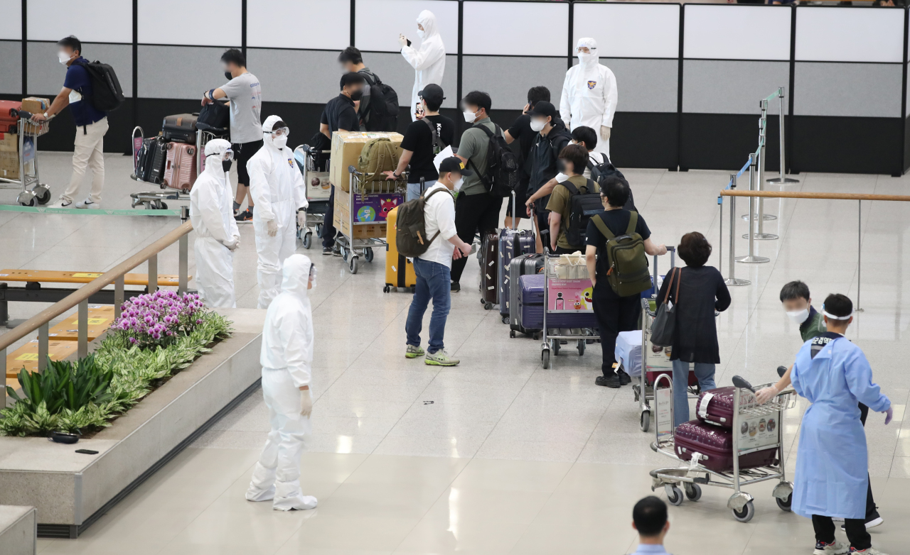South Korean residents and diplomats from India are guided by quarantine officials upon arrival at Incheon International Airport, west of Seoul, on July 13, 2021, amid the fourth wave of COVID-19. (Yonhap)