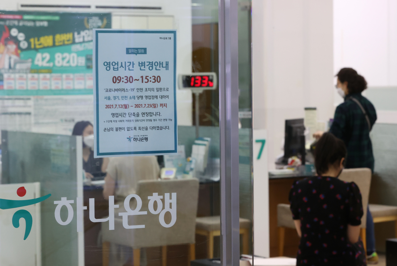 A notice shows shortened banking hours, in response to the COVID-19 resurgence, at a branch in Seoul on July 9. (Yonhap)