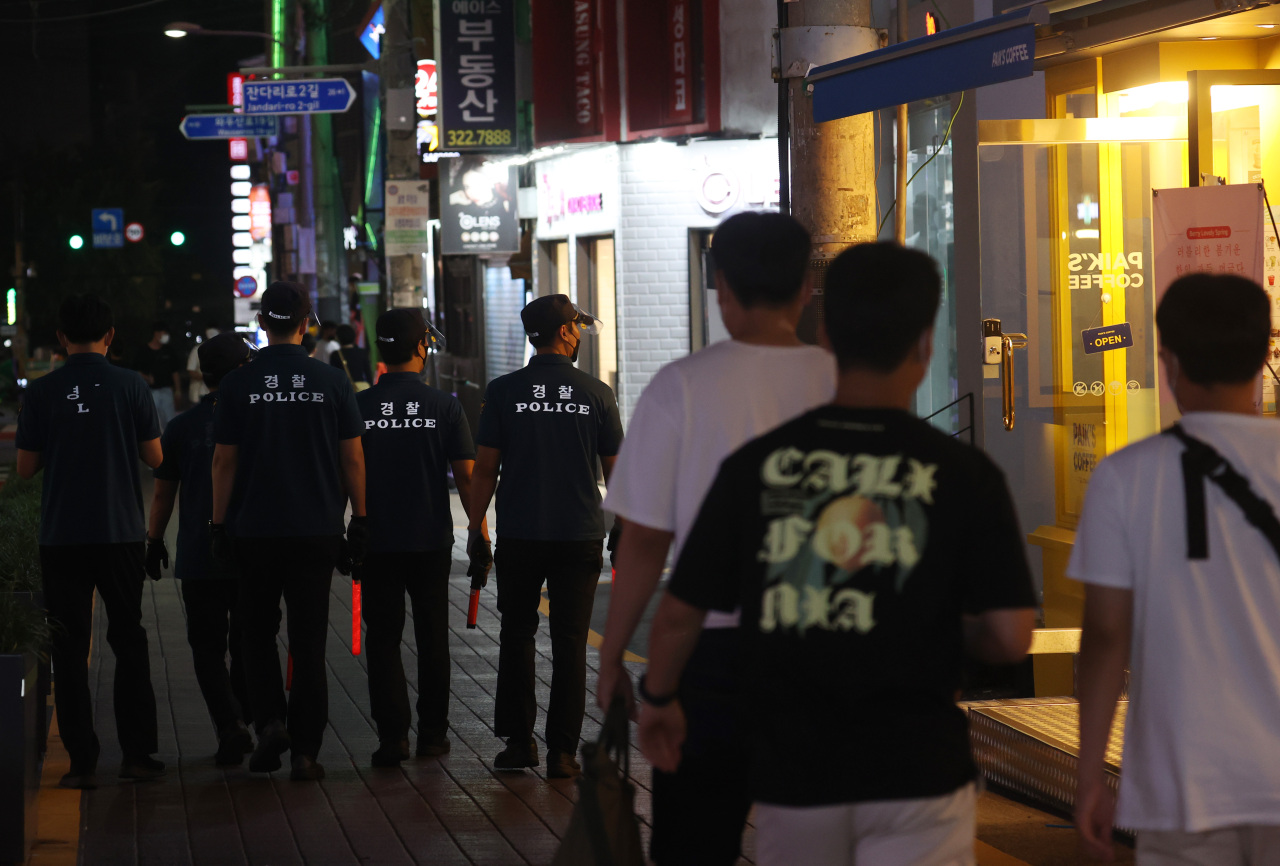 Police make rounds in Hongdae, a popular nightlife district in Seoul, to check high-risk businesses aren`t operating past the 10 p.m. curfew. (Yonhap)