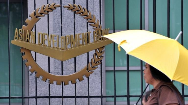 A pedestrian walks past a logo of Asian Development Bank displayed outside its headquarters in Manila. (AFP)