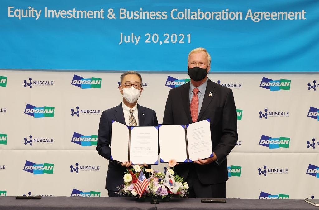High-level officials from South Korea's power plant builder Doosan Heavy Industries & Construction Co. and US small modular reactor (SMR) maker NuScale Power LLC. pose for a photo, holding an equity investment and business collaboration agreement, in the power plant builder's headquarters in Bundang, just south of Seoul on Tuesday, in this photo provided by the local company. (Doosan Heavy Industries & Construction Co.)