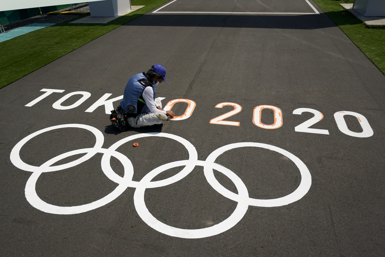 A worker paints Olympic rings at the finish line of the BMX racing track as preparations continue for the 2020 Summer Olympics, Tuesday (AP-Yonhap)