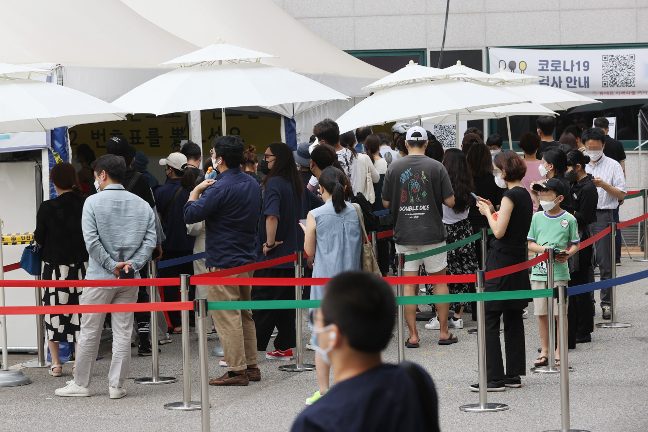 People stand in line to get COVID-19 testing at a screening station in southern Seoul on Tuesday. (Yonhap)