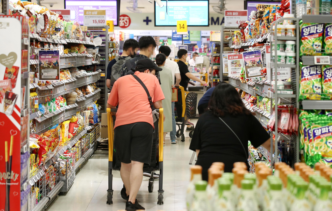Shoppers browse supermarket aisles in Seoul on Sunday. (Yonhap)