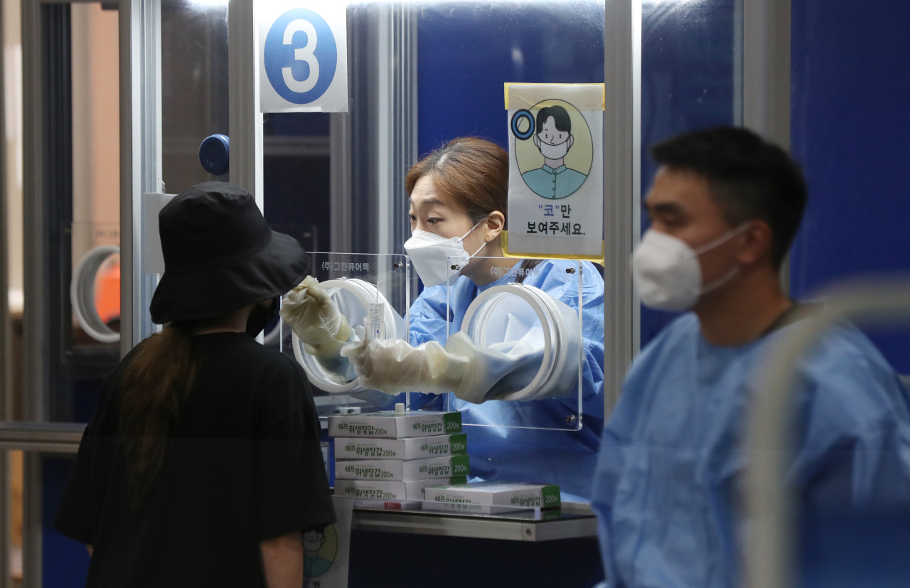 A person gets a COVID-19 test at a screening station in southern Seoul on Wednesday. (Yonhap)