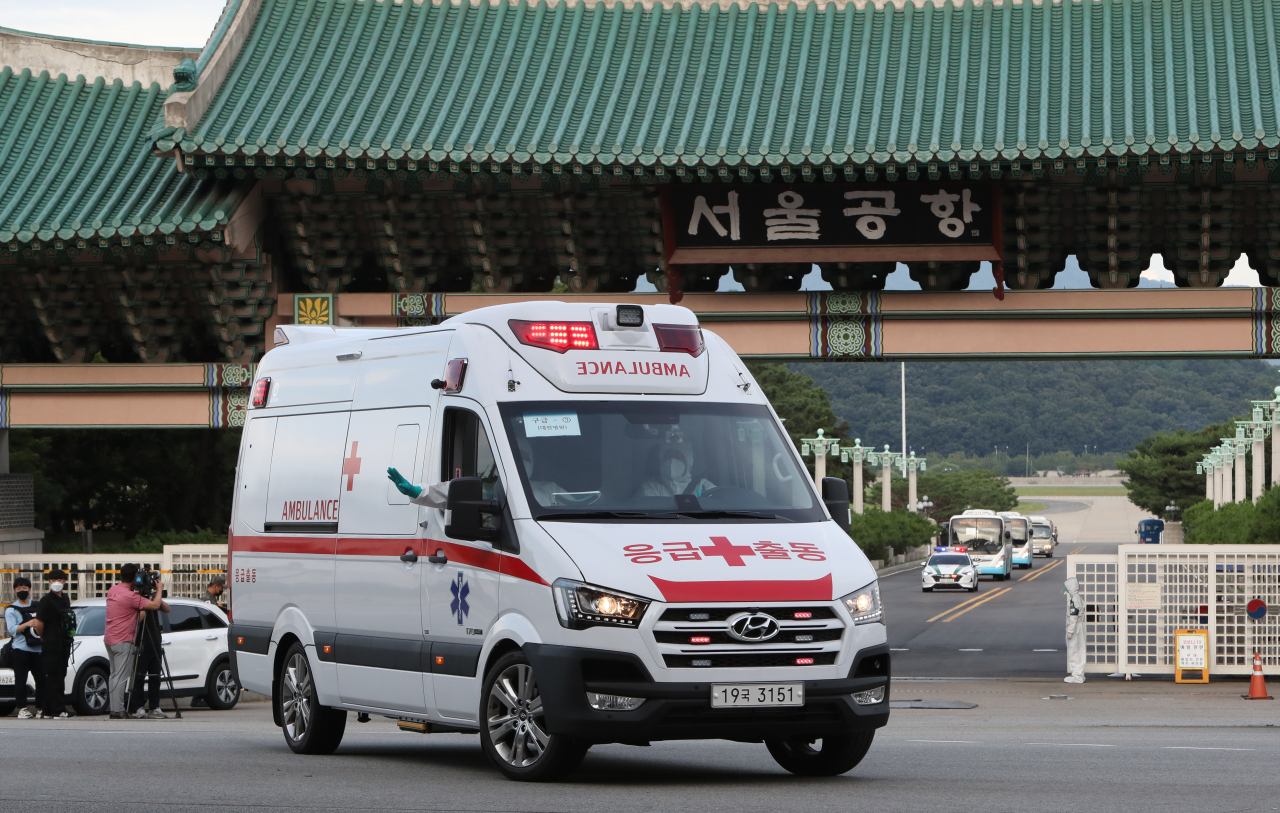 An ambulance carrying members of the Cheonghae naval unit leaves an air base in Seongnam, south of Seoul, on Tuesday, as the 301-strong unit on an anti-piracy mission off East Africa was flown home after 247 members tested positive for COVID-19. (Yonhap)