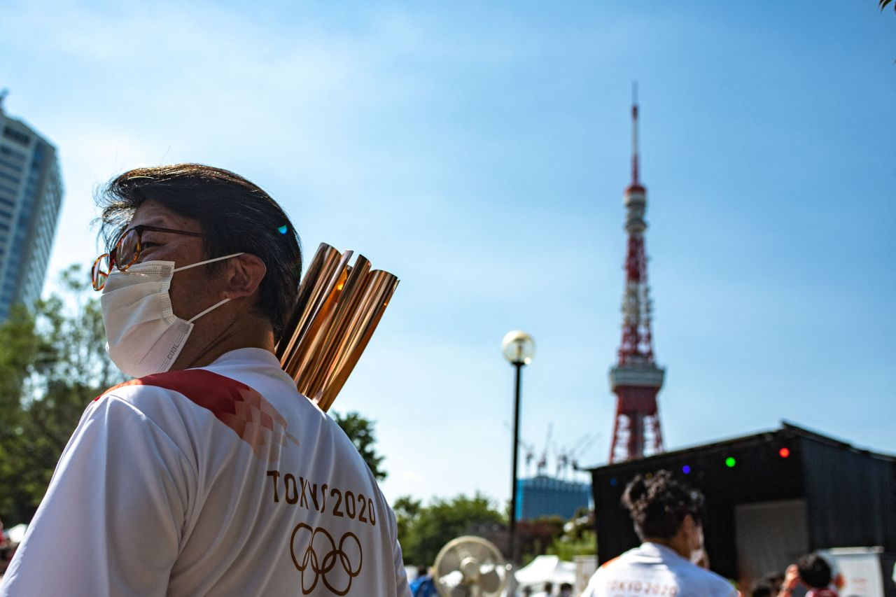 A torchbearer walks past the Tokyo Tower with his Olympic torch the after Olympic flame lighting ceremony at Shiba Park in Tokyo on July 22, 2021, ahead of the Tokyo 2020 Olympic games. (AFP-Yonhap)