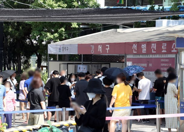 People stand in line to take COVID-19 tests at a screening station in western Seoul on Friday. (Yonhap)