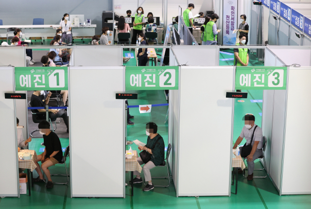 People wait for their turn for COVID-19 vaccine shots at a vaccination center in western Seoul on Thursday. (Yonhap)