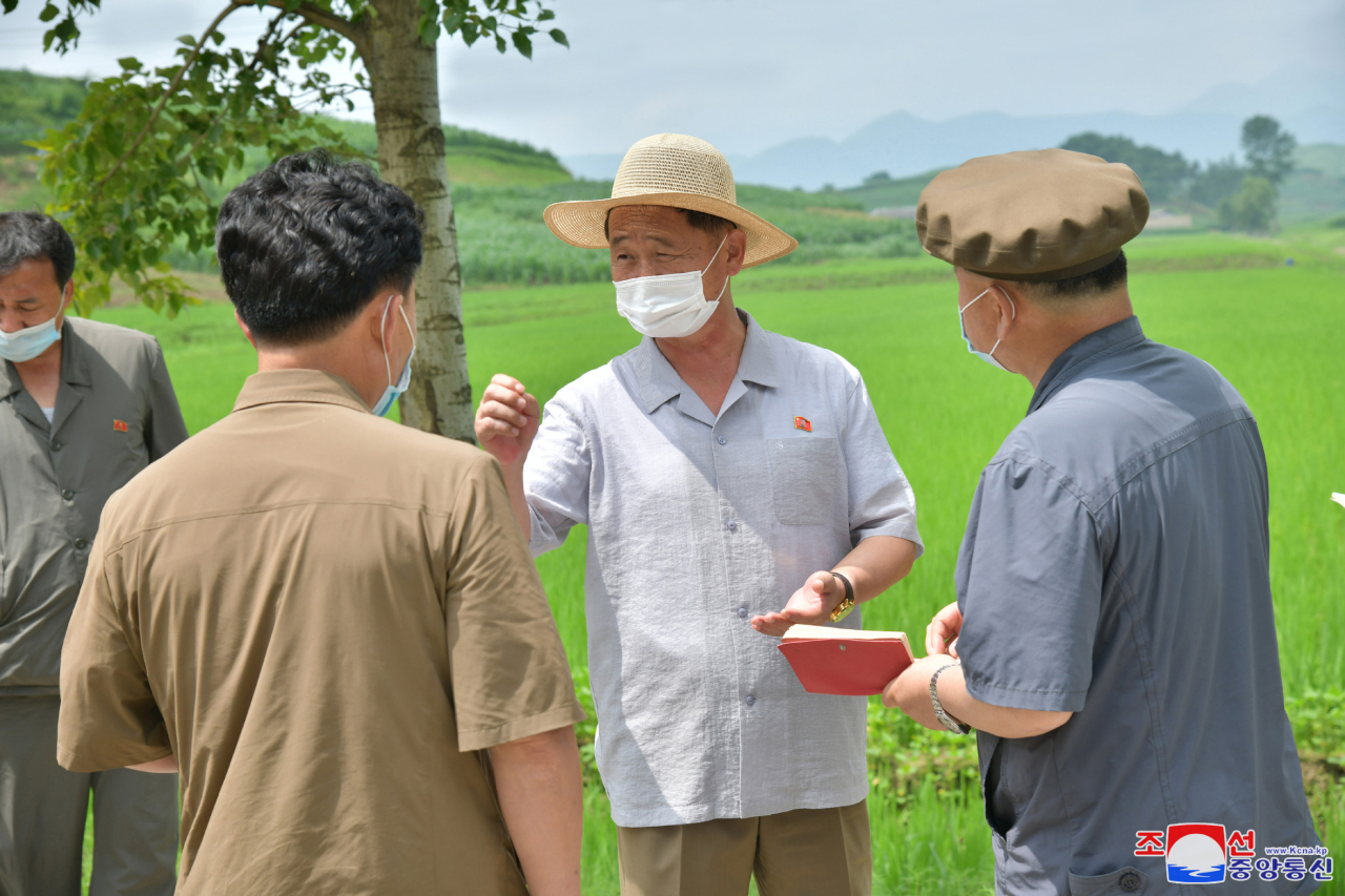 North Korean Premier Kim Tok-hun (C) visits a rice paddy at a cooperative farm as part of his inspection of fishery stations, cooperative farms, a construction site and other units in the country's eastern coastal area -- South Hamgyong and Kangwon provinces -- in this undated photo released by the Korean Central News Agency on Tuesday. (Korean Central News Agency)