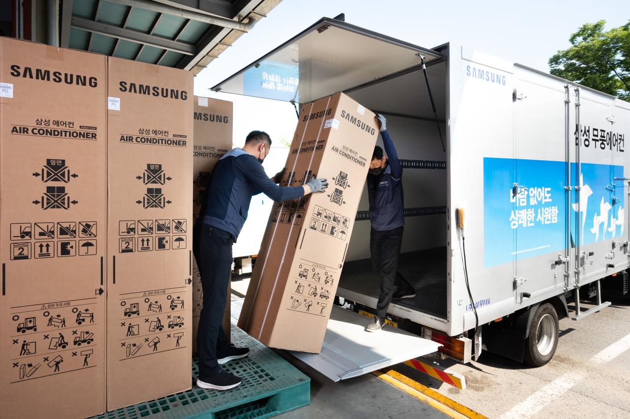This photo provided by Samsung Electronics Co. on Friday, shows two of the company's logistics workers shipping air conditioners at its warehouse in Suwon, 46 kilometers south of Seoul. (Samsung Electronics Co.)