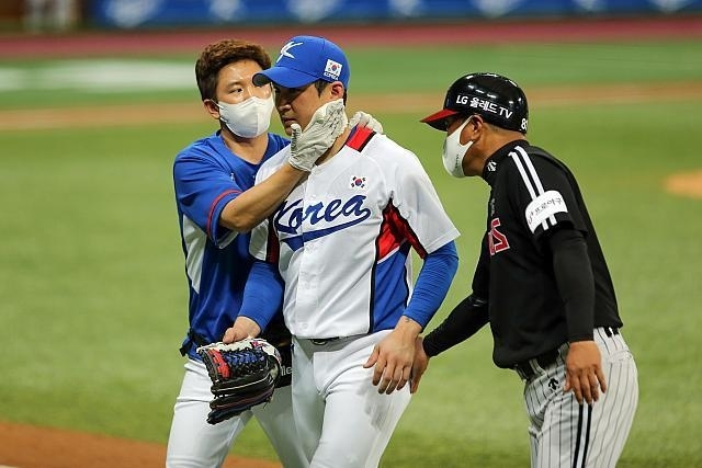 Oh Ji-hwan (C) of the South Korean Olympic baseball team is tended to by a team trainer after taking a spike from a base runner during a pre-Tokyo Olympic tuneup game against the LG Twins of the Korea Baseball Organization (KBO) at Gocheok Sky Dome in Seoul on Saturday, in this photo provided by the KBO. (KBO)