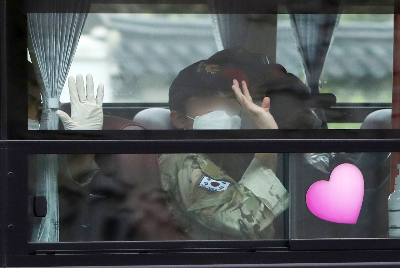 A service member of the Cheonghae Unit is waving a hand to reporters as he heads to a COVID treatment center from Seoul Air Base where the unit was airlifted from Africa on Tuesday. The anti-piracy unit, which had reported a massive COVID outbreak, cut short its mission. (Yonhap)
