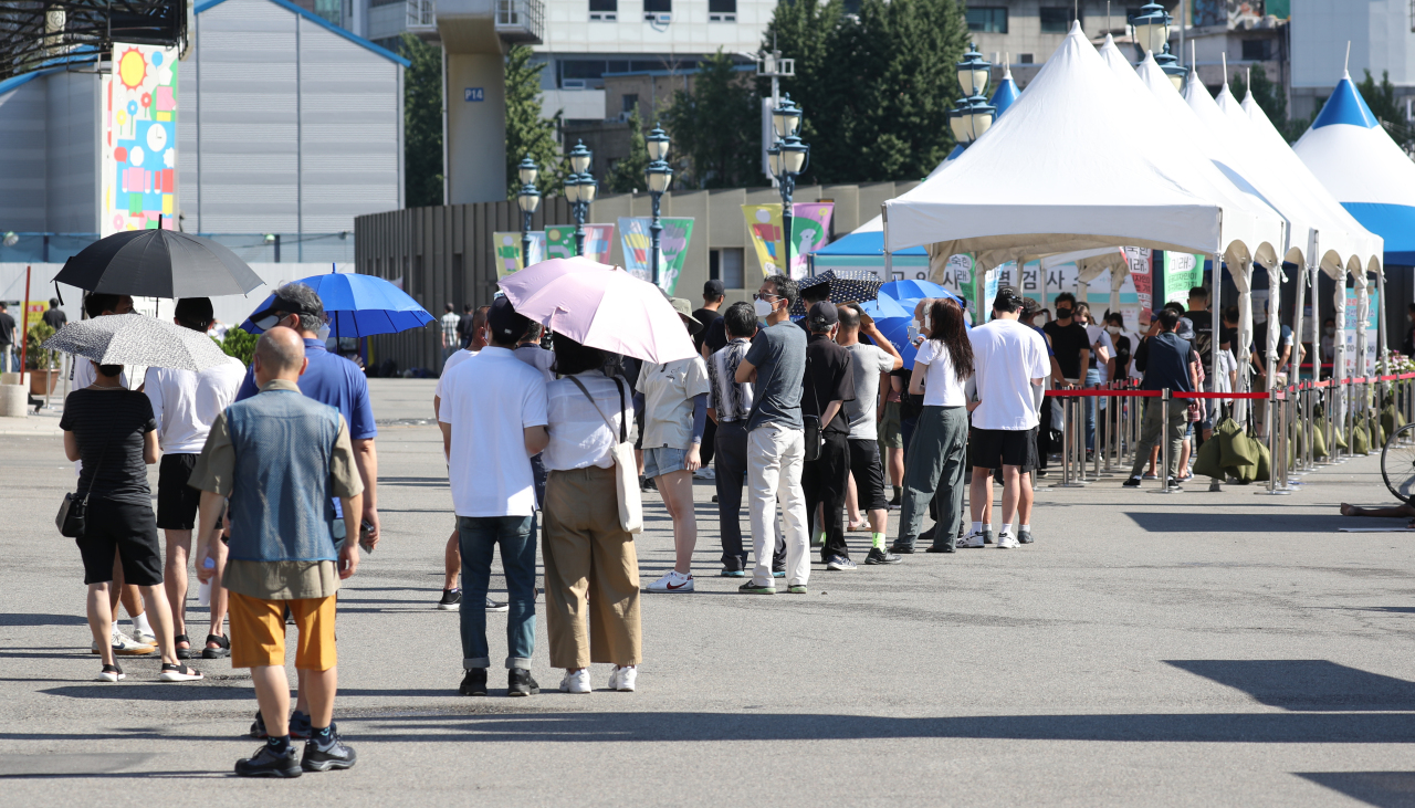 People wait in line to receive COVID-19 tests at a makeshift virus testing clinic in Seoul on Sunday. (Yonhap)