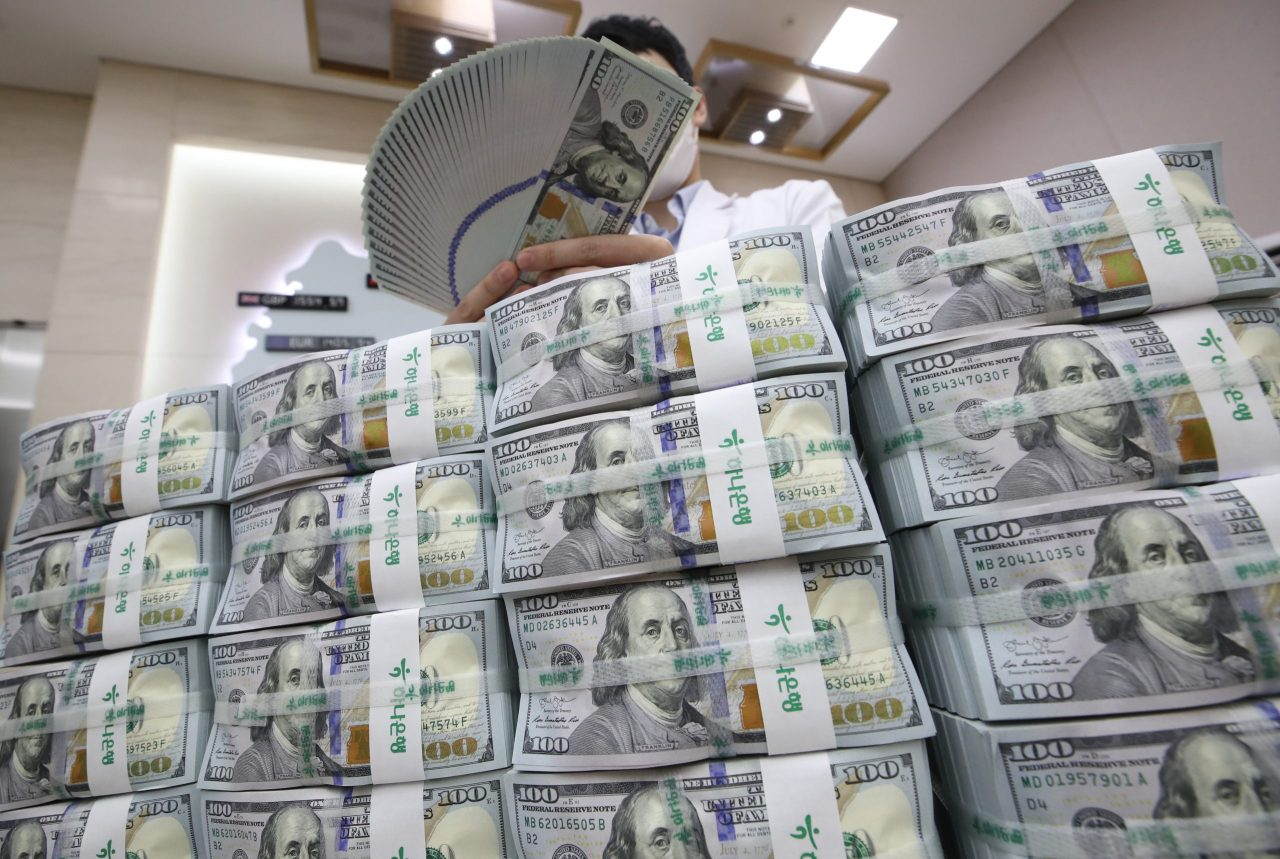 In this file photo, a bank official inspects US dollars before their release at a Seoul branch of Hana Bank. (Yonhap)
