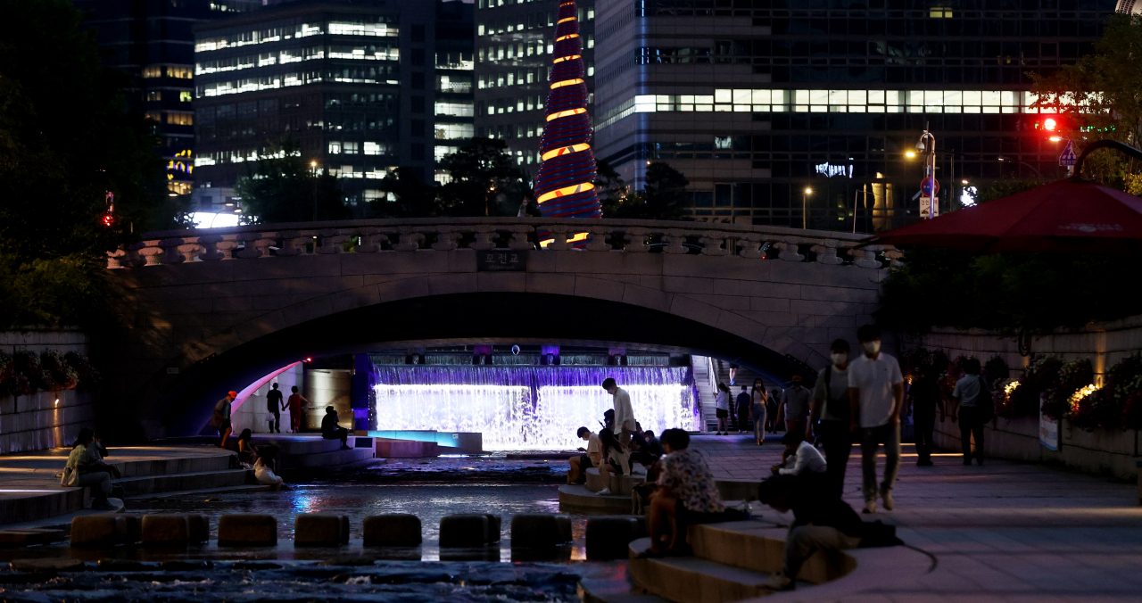 This last Thursday, photo shows people cooling off along the Cheonggye Stream in central Seoul as a scorching heat wave gripped the nation. (Yonhap)