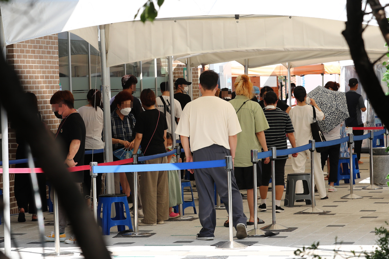 Citizens wait in line to receive COVID-19 tests at a makeshift virus testing clinic in Seoul on Monday. (Yonhap)