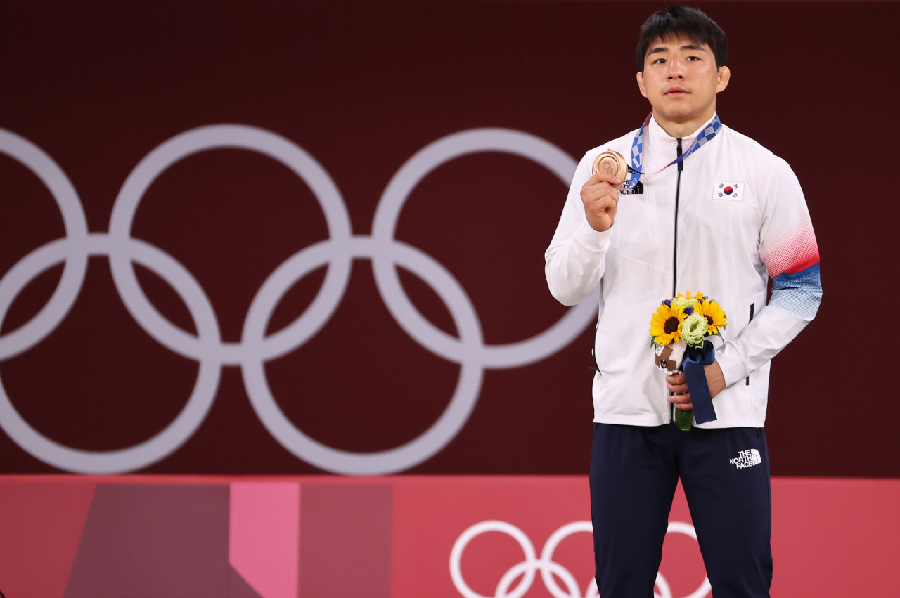 An Chang-rim of South Korea holds up his bronze medal from the men's 73kg judo event at the Tokyo Olympics at Nippon Budokan in Tokyo on Monday. (Yonhap)
