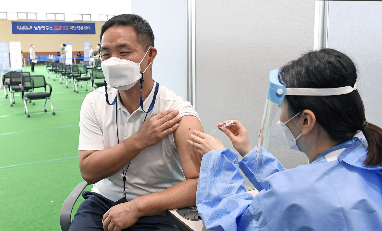 A health worker administers a COVID-19 vaccine to an employee at Hyundai Motor's Namyang R&D Center on Tuesday. (Yonhap)