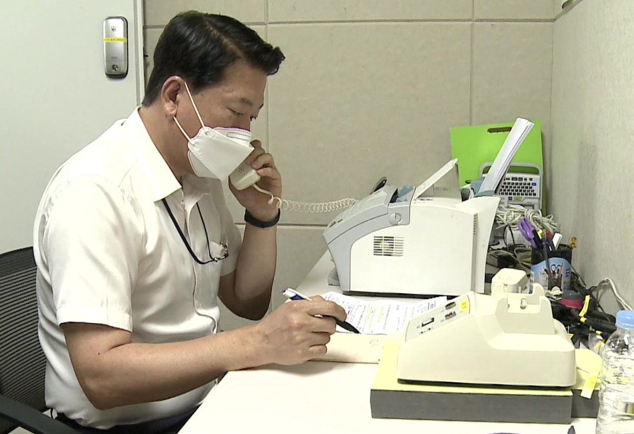This photo, provided by the unification ministry, shows a South Korean liaison officer talking to his North Korean counterpart at the Seoul bureau of their joint liaison office on Tuesday. After a 13-month suspension, the two Koreas restored cross-border communication lines that Pyongyang severed last year in protest of propaganda leaflets coming in from the South. (Unification Ministry)