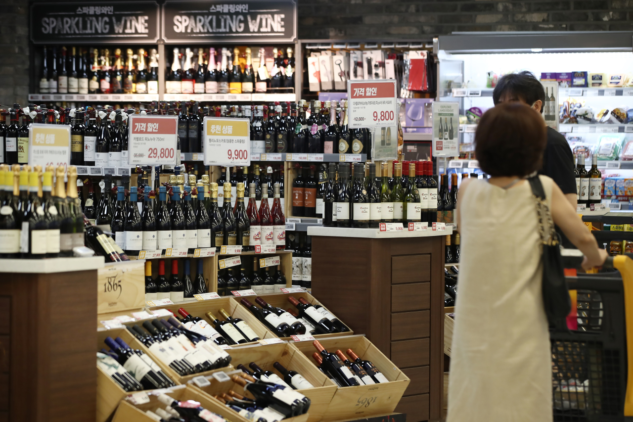 Shoppers check out the wine aisle at a supermarket in Seoul. (Yonhap)