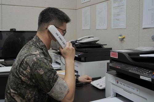 This photo, provided by the defense ministry on Tuesday, shows a South Korean service member using the inter-Korean western military communication line. (defense ministry)